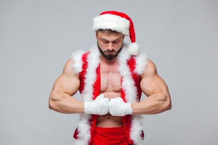 Foto de Christmas. Sexy Santa Claus . Young muscular man wearing Santa Claus hat demonstrate his muscles. Muscular Fighter kickbox With white Bandages. - Imagen libre de derechos