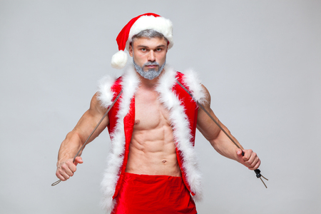 Photo for Sport, activity. Sexy Santa Claus with skipping rope. Young muscular man wearing Santa Claus hat demonstrate his muscles. on a homogeneous gray background - Royalty Free Image