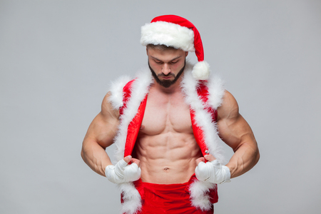 Photo for Christmas. Sexy Santa Claus . Young muscular man wearing Santa Claus hat demonstrate his muscles. Muscular Fighter kickbox With white Bandages. - Royalty Free Image