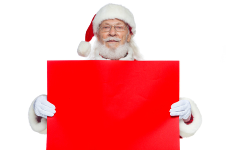 Foto de Christmas. The kind Santa Claus in white gloves holds an empty cardboard of red color. Place for advertising, for text, empty space. Copy-paste. Isolated on white background. - Imagen libre de derechos