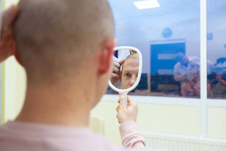 Photo for Baldness treatment. Patient suffering from hair loss in consultation with a doctor. Preparation for hair transplant surgery. The line marking the growth of hair. The patient controls the marking in the mirror - Royalty Free Image
