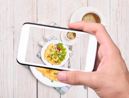 Foto de Hands taking photo egg omelette with smartphone - Imagen libre de derechos