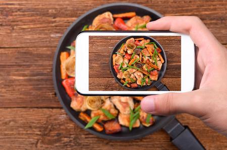 Foto de Hands taking photo meat with vegetables with smartphone. - Imagen libre de derechos