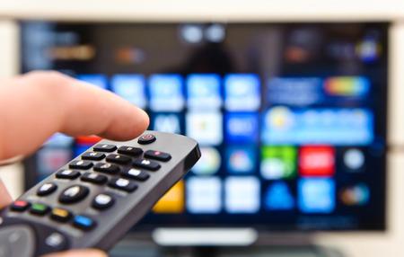 Foto de Smart tv and hand pressing remote control. - Imagen libre de derechos