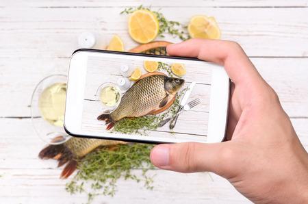 Foto de Hands taking photo fish with smartphone. - Imagen libre de derechos