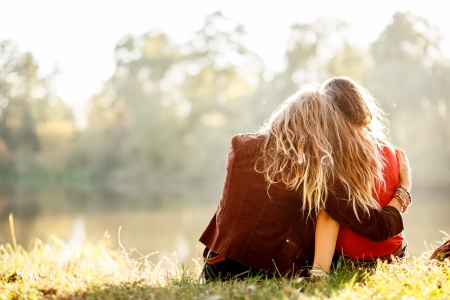 Photo for two young women sitting on grass hugging rear view - Royalty Free Image