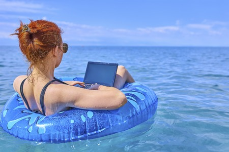 Foto de Workaholic woman working on vacation, the concept of remote work. Business woman sitting in a inflatable ring at sea and using laptop. - Imagen libre de derechos