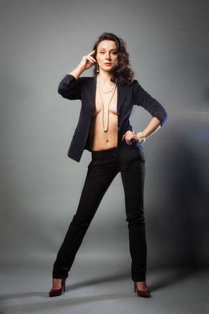 girl in a pantsuit, jacket over her body and posing