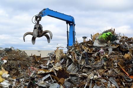 Foto de Blue hydraulic Clow Crane used for picking up scrap metal at recycling yard - Imagen libre de derechos