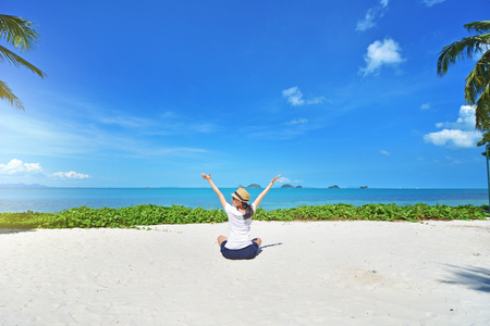 Foto de Freedom young woman with arms up outstretched to the sky with blue ocean landscape beach background - Imagen libre de derechos