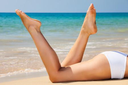 Womans  legs on the beach