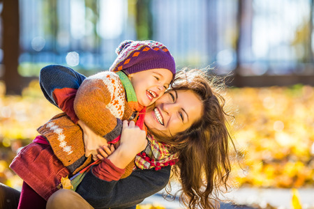 Photo pour Little girl and her mother playing in the autumn park - image libre de droit