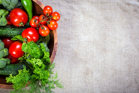 Photo pour Plenty of colorful vegetables in wooden plate on linen background - image libre de droit