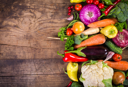 Plenty of colorful vegetables on wooden table with copy space