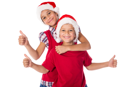Photo pour Two happy kids in Christmas hats together with thumbs up sign, isolated on white - image libre de droit