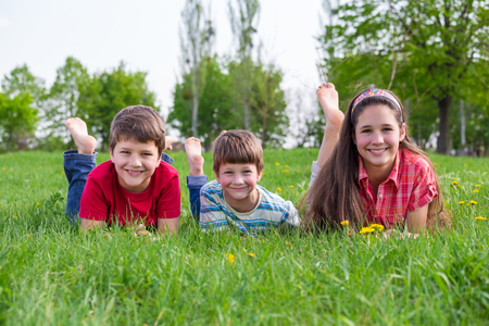 Three smiling kids lying together on green meadow