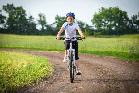 Photo pour Smiling girl ride on bike on rural landscape - image libre de droit