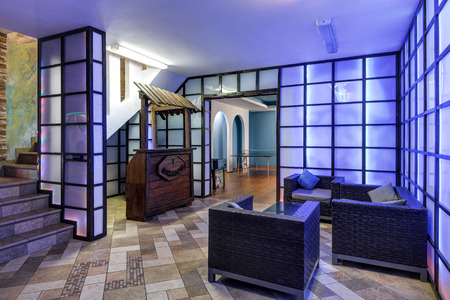 Photo for Moscow - May 2, 2018: Modern interior of residential house or hotel. Hall with armchairs and bar for relax. Interior design with purple walls and creative light. Glowing panels in room interior. - Royalty Free Image