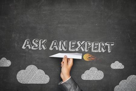 Photo pour Ask an expert concept on black blackboard with businessman hand holding paper plane - image libre de droit