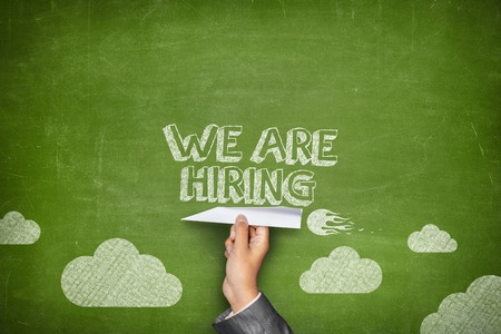 Photo pour We are hiring concept on green blackboard with businessman hand holding paper plane - image libre de droit