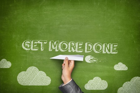 Foto de Get more done concept on green blackboard with businessman hand holding paper plane - Imagen libre de derechos