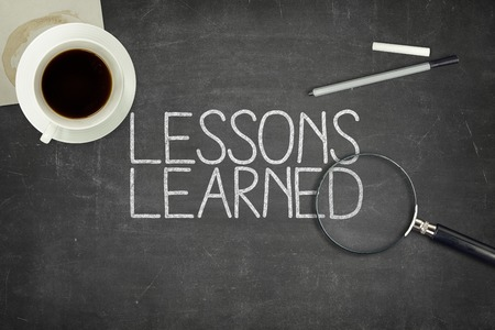 Foto de Lessons learned concept on black blackboard with coffee cupt and paper plane - Imagen libre de derechos