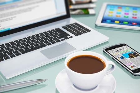 Modern office business workplace with laptop PC, touchscreen smartphone, tablet computer and white porcelain cup of black coffee
