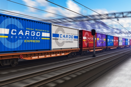 Freight train with color cargo containers passing railway station in winter with motion blur effect
