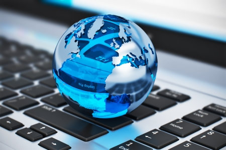 Creative abstract global communication and internet business telecommunication concept  macro view of crystal Earth globe on laptop or notebook keyboard with selective focus effect