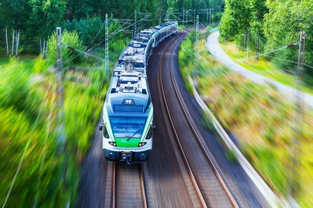 Photo pour Railroad travel and railway tourism transportation industrial concept  scenic summer view of modern high speed passenger commuter train on tracks with motion blur effect - image libre de droit