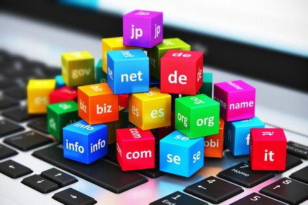 Foto de Creative abstract global internet communication PC technology and web telecommunication business computer concept: macro view of group of color cubes with domain names on laptop or notebook keyboard with selective focus effect - Imagen libre de derechos