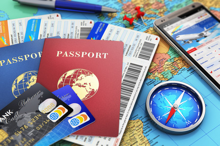 Photo for Creative abstract business travel and tourism concept: air tickets or boarding pass, passports, touchscreen smartphone with online airline tickets booking or reservation internet application, magnetic compass, credit cards and pen on world geographic map  - Royalty Free Image