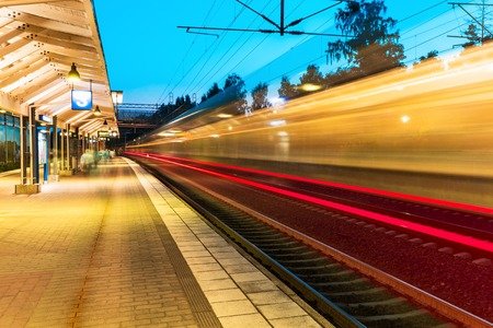 Foto de Creative abstract railroad travel and transportation industry business concept: summer evening view of high speed commuter passenger train departing from railway station platform with motion blur effect - Imagen libre de derechos