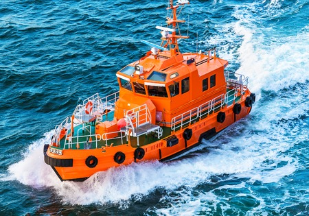 Photo pour Orange rescue or coast guard patrol boat industrial vessel in blue sea ocean water - image libre de droit