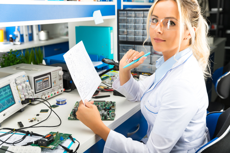 Photo pour Young attractive female digital electronic engineer checking electronic circuit in laboratory - image libre de droit