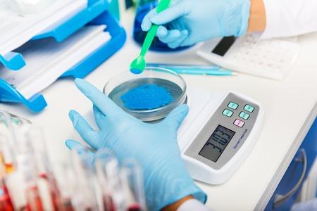 Foto de Scientist in gloves measuring weight of blue bulk solid substance in the scientific chemical laboratory - Imagen libre de derechos