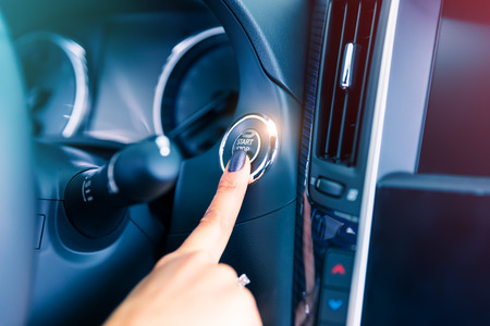 Photo pour Woman driver pushing a start ignition button switch in the modern luxury car - image libre de droit
