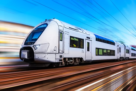 Foto per Railroad travel and railway tourism transportation industrial concept: scenic summer view of modern high speed passenger commuter train on tracks with motion blur effect - Immagine Royalty Free
