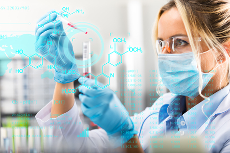 Foto de Young attractive female scientist researching in the laboratory with futuristic scientific air interface with chemical formulas and research data in the foreground - Imagen libre de derechos