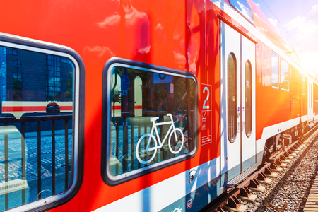 Foto per Creative abstract railroad travel and railway transportation industrial concept: modern red high speed electric passenger commuter double deck train with bicycle symbol or sign at the station platform - Immagine Royalty Free