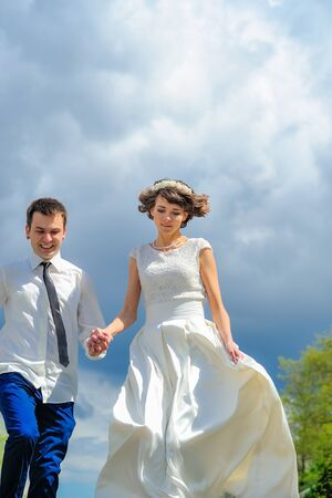 Photo for Young and handsome newlyweds on a walk in the park. Jump into happiness - Royalty Free Image