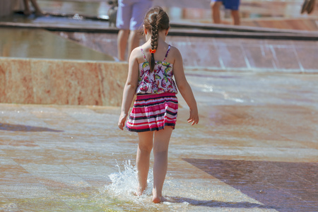 Photo for Girl jumping in the water in a fountain . - Royalty Free Image
