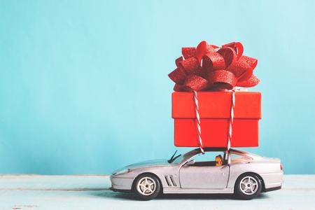 Foto de Red gift box on car toy with blue pastel color background, retro filter effect - Imagen libre de derechos