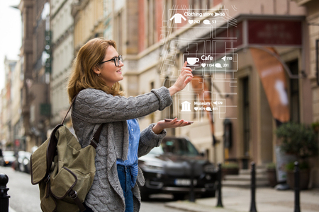 Photo pour Augmented reality in marketing. Woman traveler with phone. Navigation on the projection of the display - image libre de droit
