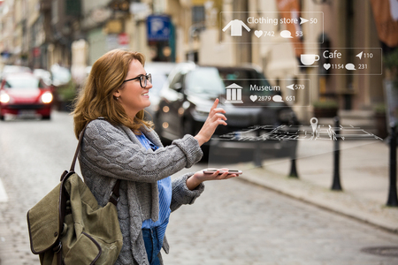 Foto de Augmented reality in marketing. Woman traveler with phone. Navigation on the projection of the display - Imagen libre de derechos