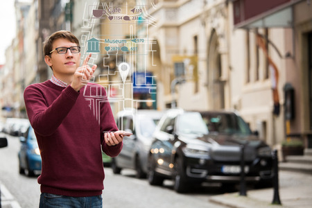 Photo pour Augmented reality in marketing. Man with phone. Navigation on the projection of the display - image libre de droit