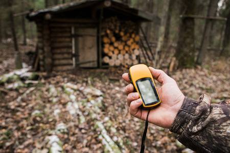 Photo for Man the hunter with a GPS navigator in the forest. hunting lodge, a backpack, a gun. Technology, Gadget. - Royalty Free Image