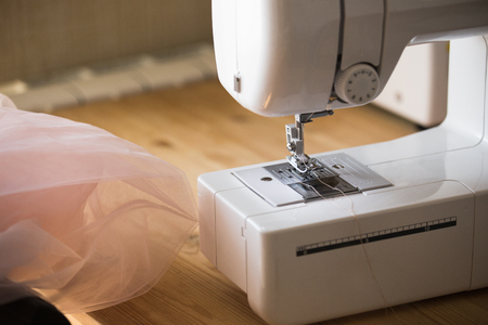 Photo pour Dress designer making wedding dresses  on sewing machine - image libre de droit