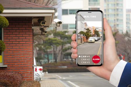 Foto de Hand with phone. On the screen interface of remote control surveillance camera - Imagen libre de derechos