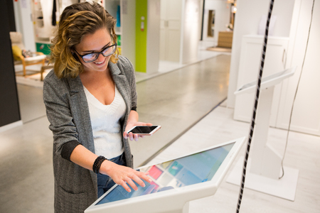 Photo pour Woman with phone configuring furniture at the self-service device in the store - image libre de droit
